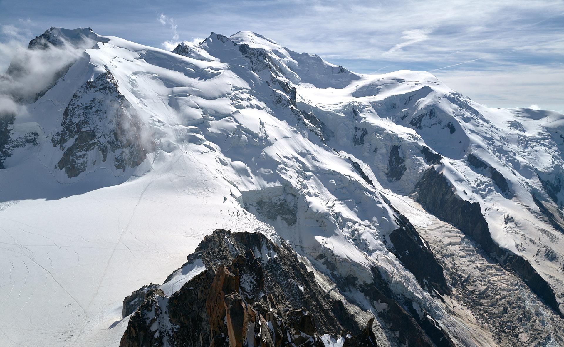 Aiguille du Midi, utsikt mot Mont Blanc. Refuge des Cosmiques i förgrunden, två klättrare på glaciären
